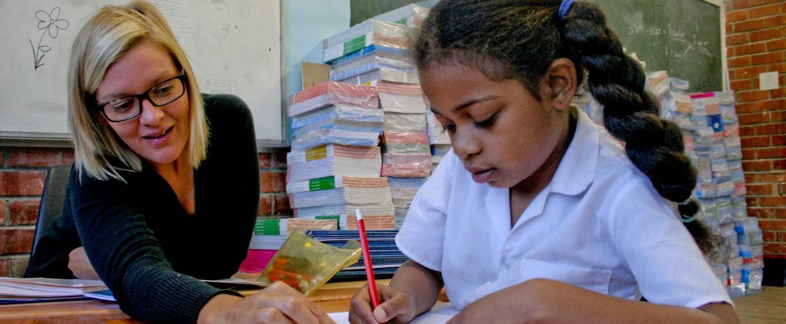 Estudiante escribe su tarea de una voluntaria de educación en Sudáfrica.